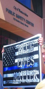 """A participant in the prayer vigil holds a sign that reads """"Blue Lives Matter"""" outside of the Public Safety Center."""