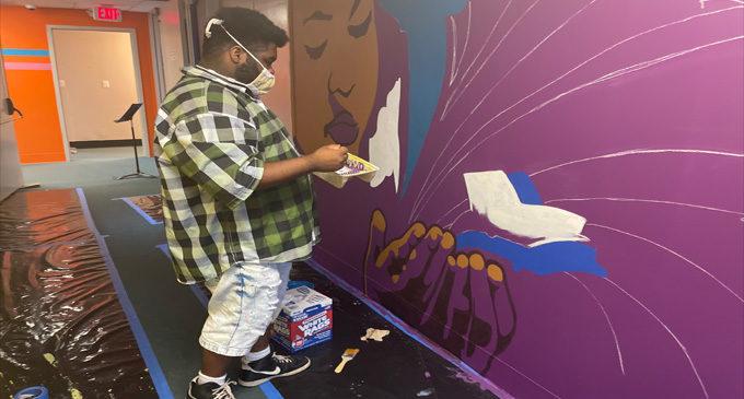 Local artist Leo Rucker and art students create murals to  brighten school hallways